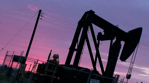 An oil derrick pumps against a purple sky Stock Video Footage