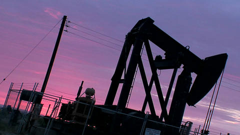 An oil derrick pumps against a purple sky Footage