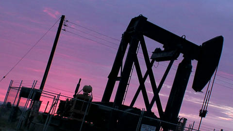 An oil derrick pumps against a purple sky Stock Video Footage