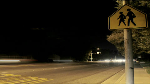A time lapse shot at night of traffic passing a crosswalk Stock Video Footage