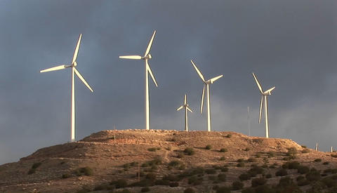 Windmills turn slowly in the sunset light and generate power on a hillside in california Footage