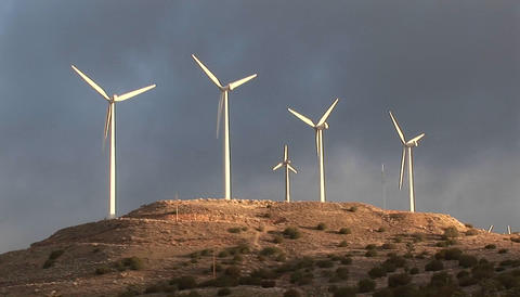 Windmills turn slowly in the sunset light and generate... Stock Video Footage