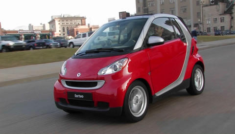 A man driving a red Smart car through a city Stock Video Footage