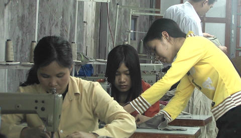 An Asian woman instructs a seamstress who sits at a... Stock Video Footage