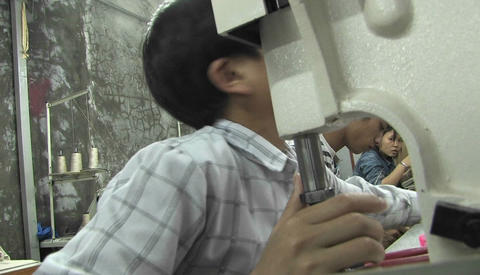 A child trying to fix a sewing machine with the help of a... Stock Video Footage