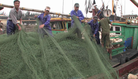 Men gather fishing nets from a boat Stock Video Footage