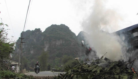 Burning leaves near a mountain road Stock Video Footage
