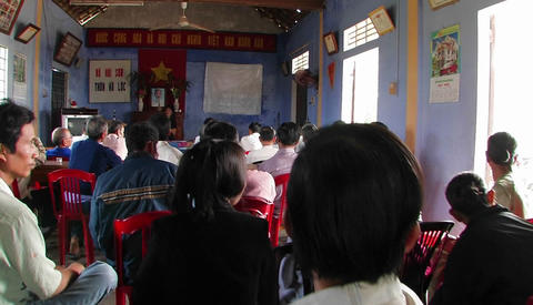 A woman speaking Vietnamese in front of a seated audience Footage