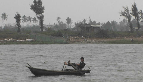 A young boy is sailing a boat in a river rowing with his feet on the Mekong River in Vietnam Footage