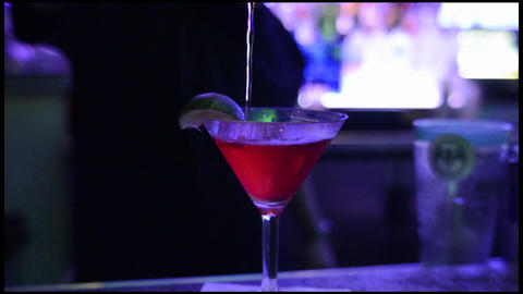 Bartender pouring a shaken cocktail into a chilled Footage