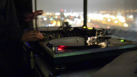 Disc Jockey spinning records on two turntables and Footage