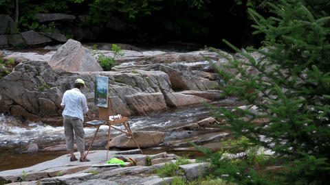 An artist paints a picture beside a river in natur Stock Video Footage