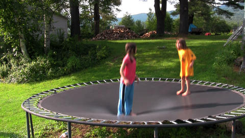 Kids jump and play on the trampoline in the backya Footage