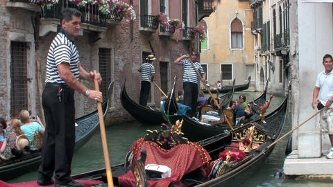 Gondolas take people through a narrow canal with b Footage