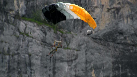 A man paraglides through a mountain pass near a wa Stock Video Footage