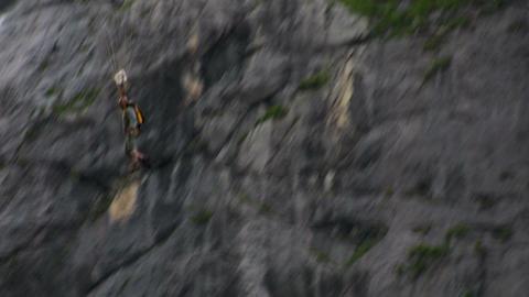 A man paraglides through a mountain pass near a wa Stock Video Footage