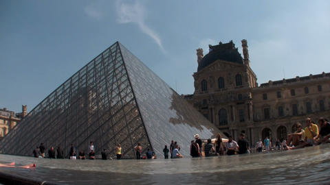 Crowds of people walk around the grounds of Louvre Footage