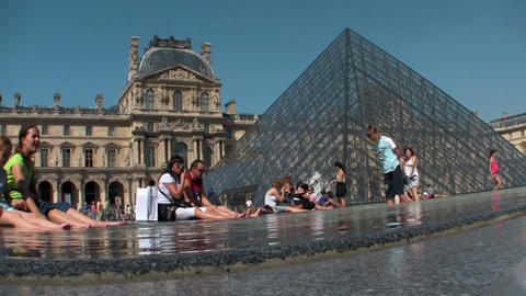 People sit in front of the Louvre in Paris Footage