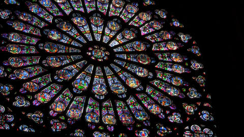 A round stained glass window in a darkened cathedr Footage