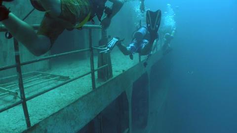 Divers explore a shipwreck Stock Video Footage