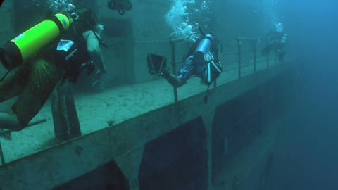 Divers explore a shipwreck Stock Video Footage