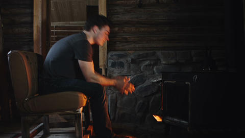 Man Warming in front of a Slow Burning Stove Live Action