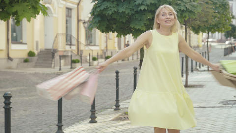 Charming cheerful woman spinning with shopping bags on sunny city street Live Action