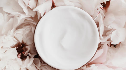 Anti-aging face cream jar and peony flowers, clean moisturizer as skin care Live Action