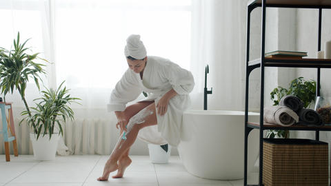 Beautiful young woman in bathrobe shaving legs caring for body in bathroom Live Action