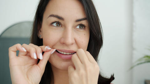 Smiling girl taking care of teeth using dental floss during morning activities Live Action