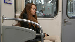 Woman sit alone at running subway train, faint smile on sad face Footage