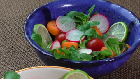 Bowl of fresh vegetable salad on jute table cloth. Healthy food Live Action