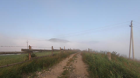 Man walks along dirt path on mountaintop, under which there is morning fog Live Action