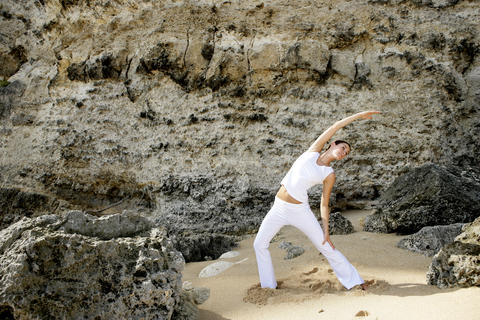 Young woman practicing yoga on the beach 相片