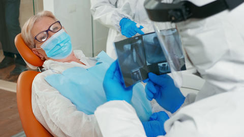 Doctor with face shield reviewing panoramic dental x-ray image Live Action