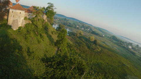 Colorful hot air balloons fly over the medieval castle and lake in the morning Live Action