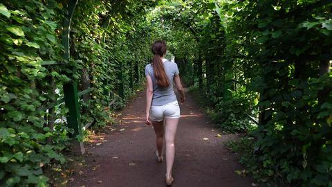 Adult woman walk inside green pergola tunnel, camera follow behind Footage