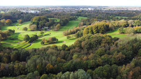 Overhead Aerial Drone Shot over Trees & Road towards UK Golf Course & Town (4K) Live Action