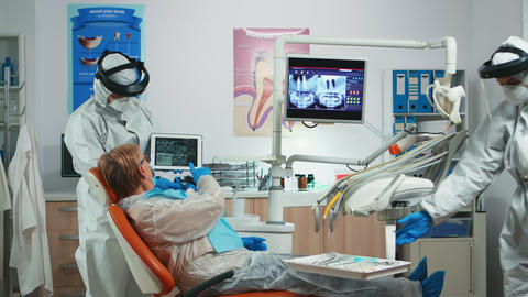 Dentist in coverall examining x-ray image on tablet Live Action