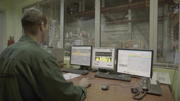 Factory worker controls the production using computers Footage