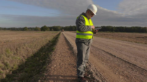 Road construction engineer using tablet on road Footage
