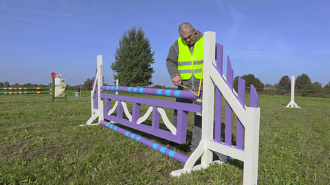 Horse handler with measure tape near hurdle Footage