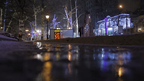 Street decorated for the Christmas celebration and reflection on a puddle Footage