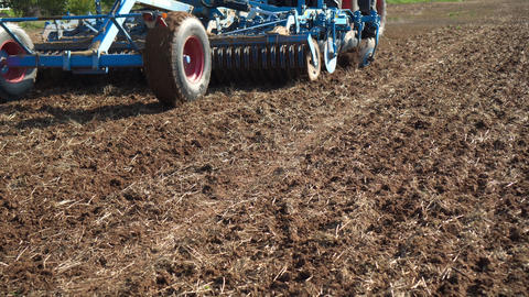 Tractor discing stubble field with special equipment cultivating farm land soil Live Action