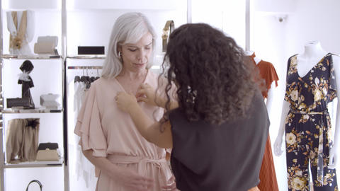 Black haired seller helping female customer to try on new dress Live Action