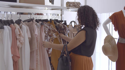 Black haired lady choosing clothes and browsing dresses Live Action