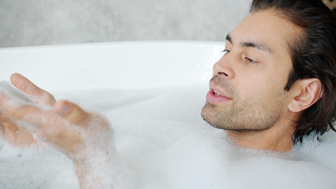 Happy mixed race man blowing foam relaxing in bathtub and having fun in bathroom Live Action