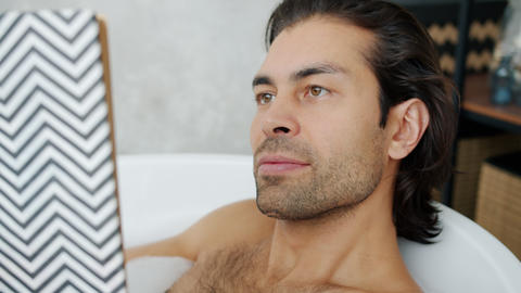 Close-up portrait of attractive young brunet reading book in bathtub smiling Live Action