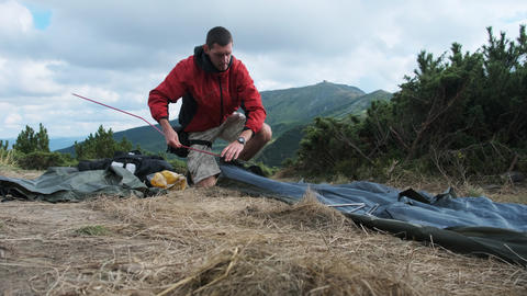 Tourist Traveler Sets Up a Single Tent in the Mountains. Hiking. Solo Tourism Live Action