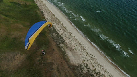 Paraglider is flying over the hills along the seashore, nature and sports Live Action